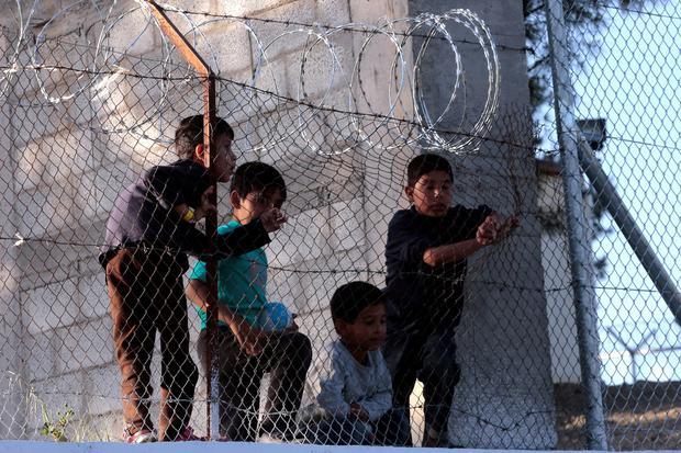 Refugee children inside Moria detention center watch protest organized by Greek solidarity group demanding closing of detention center in Moria on April 15, 2016 in Mytilini on Lesbos island in Greece. (Photo by Milos Bicanski/Getty Images)