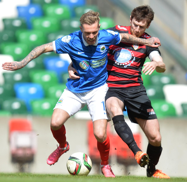 Strength: Kirk Millar grapples with Coleraine defender Howard Beverland