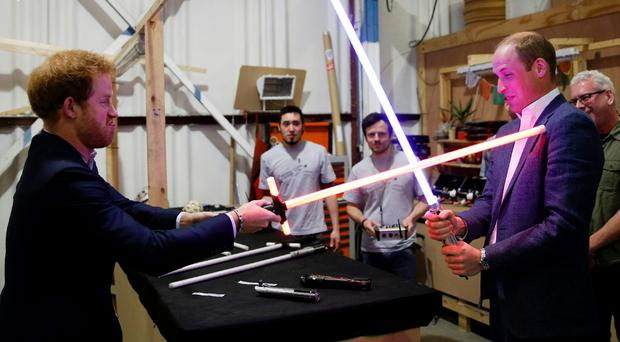 Britain's Prince Harry (L) and Prince William, Duke of Cambridge try out light sabres during a tour of the Star Wars sets at Pinewood studios in Iver Heath, west of London on April 19, 2016. Prince William and Prince Harry are touring Pinewood to visit the production workshops and meet the creative teams working behind the scenes on the Star Wars films. / AFP PHOTO / ADRIAN DENNISADRIAN DENNIS/AFP/Getty Images