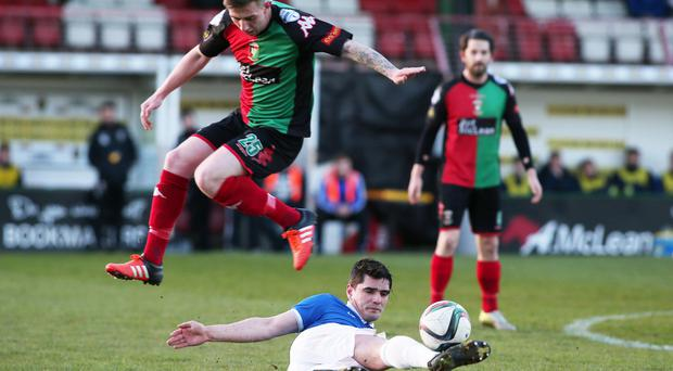 Sliding in: Linfield ace Jimmy Callacher takes to the ground to steal possession from Glentoran's Jonathan Smith at The Oval