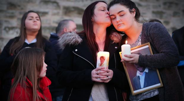Widow Joanne McGibbon (centre) with her daughters Michaela and Seana and Fr Gary Donegan joins members of the public at a vigil in the grounds of Holy Cross Church, Ardoyne, in support of the family of taxi driver and father-of-four Michael McGibbon who was shot dead in North Belfast at the weekend.