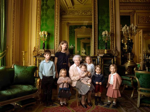 This handout portrait picture taken by US photographer Annie Liebovitz shows Queen Elizabeth II (C) posing with her two grandchildren, James, Viscount Severn (L) and Lady Louise (2L) and her five great-grandchildren Mia Tindall (holding handbag), Savannah Philipps (3R), Isla Phillips (R), Prince George (2R) and Princess Charlotte (C) in the Green Drawing room at Windsor Castle in Windsor. This picture is one of three official photographs released by Buckingham Palace to mark Queen Elizabeth II's 90th birthday. / AFP PHOTO / ANNIE LEIBOVITZ/AFP/Getty Images