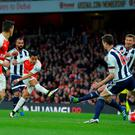 Well hit: Alexis Sanchez drives the ball past West Bromwich Albion's two Northern Ireland defenders Jonny Evans and Gareth McAuley for Arsenal's first goal