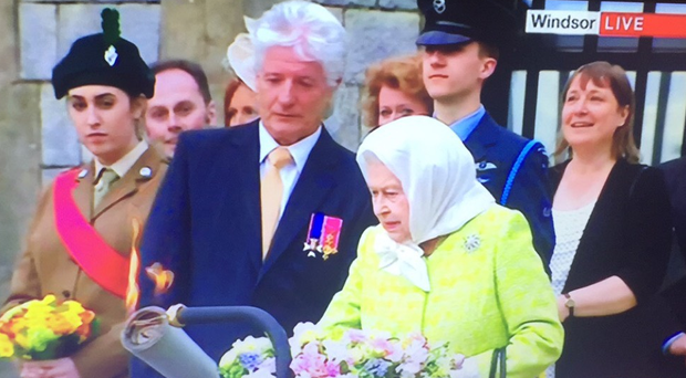 Ballymena cadet Emma-Lee Wray stands holding flowers as the Queen lights the first of her 90th birthday beacons. Picture: Screengrab BBC