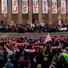 "People hold Liverpool football scarves in the air as they sing ""You'll Never Walk Alone"" outside St George's Hall in Liverpool, north west England on April 27, 2016, during an event held in remembrance of the 96 Liverpool fans who died in the 1989 Hillsborough football stadium disaster. AFP/Getty Images"