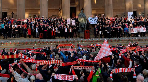 People hold Liverpool football scarves in the air as they sing