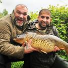 A load of carp: Neil Ruddock and his new pal make a splash, while Ali Hamidi looks on