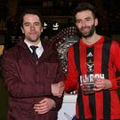 Shake on it: Emmet McEvoy from Toals presents Darren Campbell of Harryville Homers with his man of the match award
