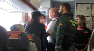 Two women from Northern Ireland are escorted off a plane by the Spanish authorities.