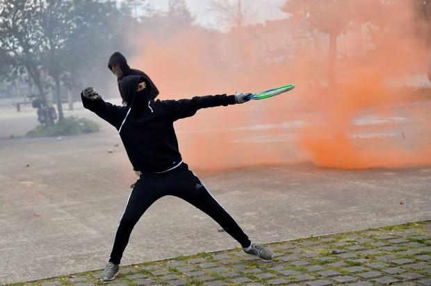 A young man holding a tennis racket throws a projectile at anti-riot police (not pictured) during clashes within a demonstration against the French government's proposed labour reforms on April 28, 2016 in Nantes. AFP/Getty Images