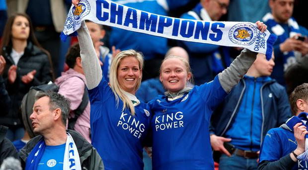 Leicester City fans hold up a 'Champions' scarf in the stands after the final whistle during the Barclays Premier League match at Old Trafford, Manchester. Picture by Martin Rickett/PA Wire