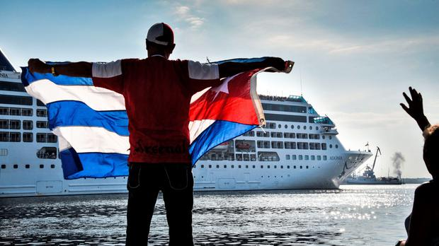 A man waves a Cuban flag at the Malecon waterfront as the first US-to-Cuba cruise ship to arrive in the island nation in decades glides into the port of Havana, on May 2, 2016. AFP/Getty Images