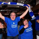 LEICESTER, UNITED KINGDOM - MAY 02: Leicester City fans celebrate as their team becomes Premier League champions after watching the Barclays Premier League between Chelsea and Tottenham Hotspur at Yates's Bar on May 2, 2016 in Leicester, United Kingdom. Spurs' failure to win against Chelsea tonight sees Leicester City claim their first ever top flight title. (Photo by Ross Kinnaird/Getty Images)