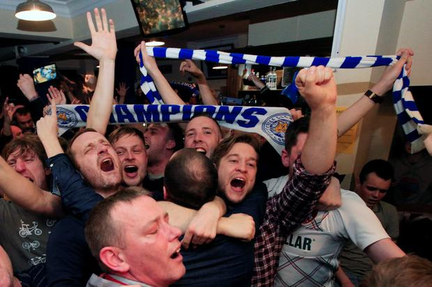 Leicester City fans celebrate in the Market Tavern in Leicester after seeing their side crowned Barclays Premier League champions following Tottenham Hotspur's 2-2 drew against Chelsea. PA