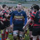 Job well done: Banbridge ace Jason Griffin leads his team off the pitch after their 22-7 victory over Rainey, who gave the new UCL2 champions a guard of honour