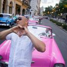 "U.S. Actor Vin Diesel gestures to the crowd watching the presentation of fashion designer Karl Lagerfeld's ""cruise"" line for fashion house Chanel, at the Paseo del Prado street in Havana, Cuba, Tuesday, May 3, 2016. With the heart of the Cuban capital effectively privatized by an international corporation under the watchful eye of the Cuban state, the premiere of Chanel 2016/2017 ""cruise"" line offered a startling sight in a country officially dedicated to social equality and the rejection of material wealth. (AP Photo/Ramon Espinosa)"