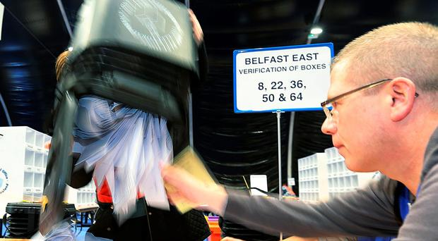 Volunteers empty a ballot box in the counting centre at the Titanic Exhibition Centre, Belfast