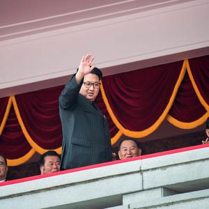 TOPSHOT - North Korean leader Kim Jong-Un (C) waves as he walks past top-ranking party officials from a balcony of the Grand People's Study House following a mass parade marking the end of the 7th Workers Party Congress in Kim Il-Sung Square in Pyongyang on May 10, 2016. North Korea kicked off a massive parade in the centre of Pyongyang on May 10 to celebrate a just-concluded ruling party congress that was seen as a formal coronation for supreme leader Kim Jong-Un. / AFP PHOTO / Ed JonesED JONES/AFP/Getty Images