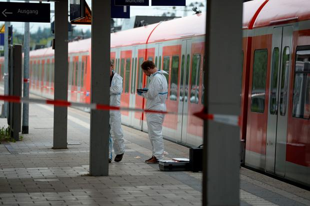Forensic experts of the police stand next to a commuter train standig on a platform of the train station of Grafing near Munich, southern Germany, where a man killed one person and wounded three others in a knife attack on May 10, 2016. AFP/Getty Images
