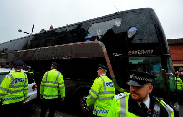 The bus carrying the Manchester United team is escorted by police after having a window smashed on its way to West Ham's Boleyn ground. /AFP/Getty Images