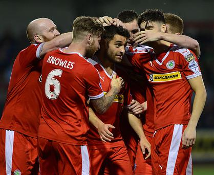 Cliftonville's David McDaid is mobbed after scoring his team's third goal against Glentoran in the Europa League play-off game