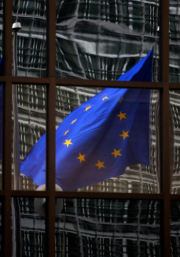 A European flag reflects 06 November 2007 in a building of the EU headquarters in Brussels