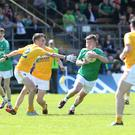Holding tight: Colm Jones of Fermanagh protects the ball under pressure from Antrim's Eoin Nagle