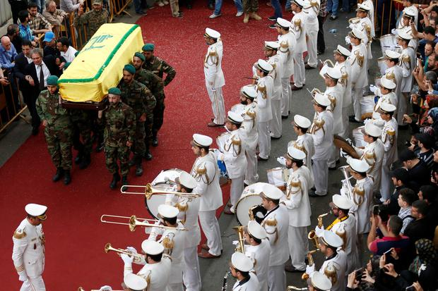 Hezbollah fighters carry the coffin of their slain commander Mustafa Badreddine, draped in a Hezbollah flag, during his funeral procession in a southern suburb of Beirut, Lebanon, Friday, May 13, 2016. (AP Photo/Hassan Ammar)