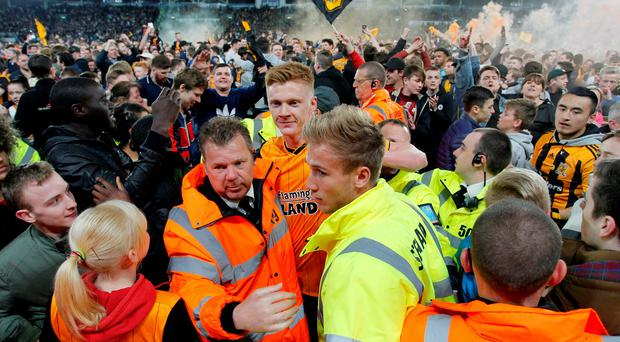 Party time: Sam Clucas leaves the pitch as Hull celebrate reaching Wembley