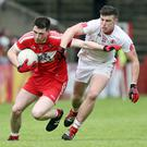 Arm's length: Derry's Gareth McKinless holds off the challenge of Connor McAliskey of Tyrone