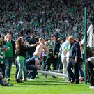Hibernian fans invade the Hampden Park pitch at the final whistle as Hibernian beat Rangers 3-2 during the William Hill Scottish Cup Final between Rangers FC and Hibernian FC at Hamden Park on May 21, 2016 in Glasgow, Scotland. (Photo by Mark Runnacles/Getty Images)