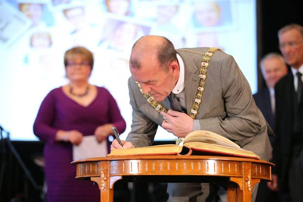 Lord Mayor Arder Carson signs the Honorary Burgess Book at the Freedom of the City of Belfast ceremony in Belfast City Hall. Photo by Kelvin Boyes / Press Eye.