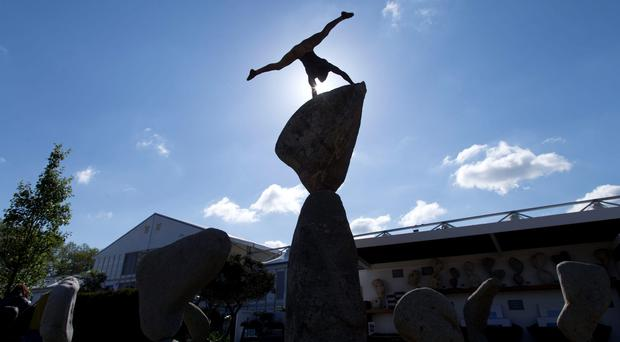 A gymnast balances on the Adrian Gray Stone balancing sculpture at the Chelsea Flower Show at the Royal Hospital Chelsea in London. Pic: Yui Mok/PA Wire