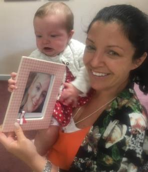 Louise James and baby Rioghnach-Ann hold a photo of Jodie Lee at St Mary's College