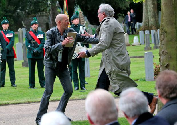 26/05/16 Kevin Vickers Ambassador of Canada to Ireland (wearing light coloured mac jacket) tackles a protestor who attempted to disrupt proceedings during a State ceremony to remember the British soldiers who died during the Easter Rising, 1916 pictured this morning at Grangegorman Military Cemetery..Picture Colin Keegan, Collins Dublin.