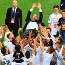 On top of the world: Zinedine Zidane is held aloft by Real Madrid players
