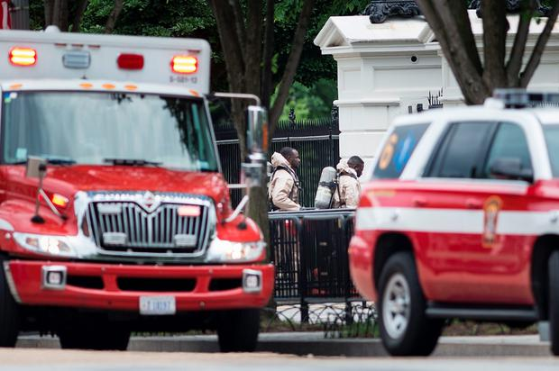 Emergency personnel in protective suits walk to the Northeast gate to the White House from Pennsylvania Avenue during a security lockdown of the White House grounds May 30, 2016 in Washington, DC. / AFP PHOTO / Brendan SmialowskiBRENDAN SMIALOWSKI/AFP/Getty Images