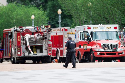 A member of the Secret Service walks past firetrucks and ambulances on Pennsylvania Avenue during a security lockdown of the White House grounds May 30, 2016 in Washington, DC. / AFP PHOTO / Brendan SmialowskiBRENDAN SMIALOWSKI/AFP/Getty Images