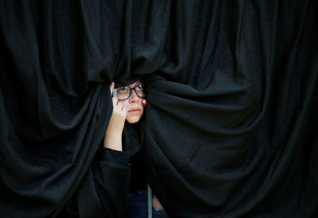 A girl watches Democratic presidential candidate Hillary Clinton speak at a rally at Hartnell College, Wednesday, May 25, 2016, in Salinas, Calif. (AP Photo/John Locher)