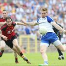 Getting his kicks: Monaghan's Kieran Hughes fires in a shot despite pressure from Down's Joe Murphy and Conaill McGovern