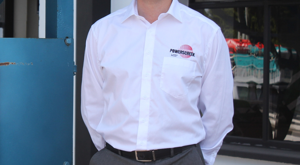 Global product director Colin Clements in front of a plaque marking Powerscreen's 50th anniversary