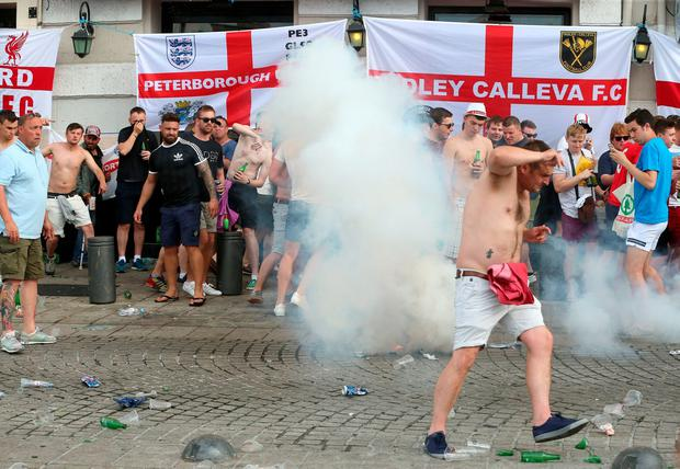 French police fire tear gas as they clash with English football fans at The Queen Victoria pub in Marseille ahead of the first game in Euro 2016. PA