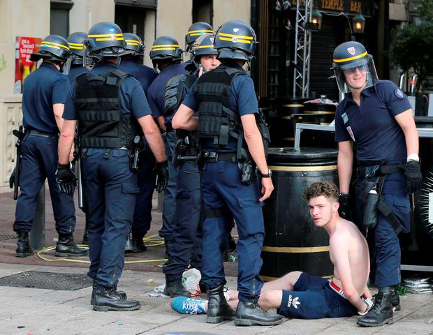 French police restrain a man following clashes with English football fans outside The Queen Victoria pub in Marseille ahead of the first game in Euro 2016. PA