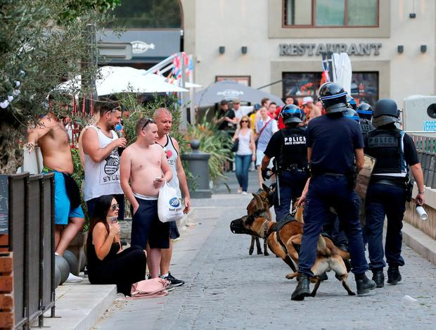 French police dog handlers walk past football fans following clashes with English football fans outside The Queen Victoria pub in Marseille ahead of the first game in Euro 2016. PA