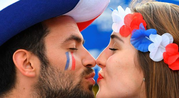The beautiful game - football fans from around the world - -A man and a woman supporting France kiss prior to the Euro 2016 group A football match between France and Romania at Stade de France, in Saint-Denis, north of Paris