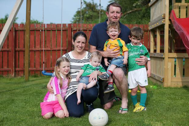 Split loyalties: Former Fermanagh player Ronan Gallagher pictured at home in Armagh with his wife Catherine and children Joe (4), Grainne (5), Shay (1) and Micheal (7 months)