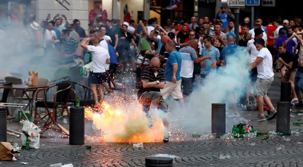 A tear gas canister explodes under a football fan as England supporters clash with police in Marseille last night. Photo by Carl Court/Getty Images
