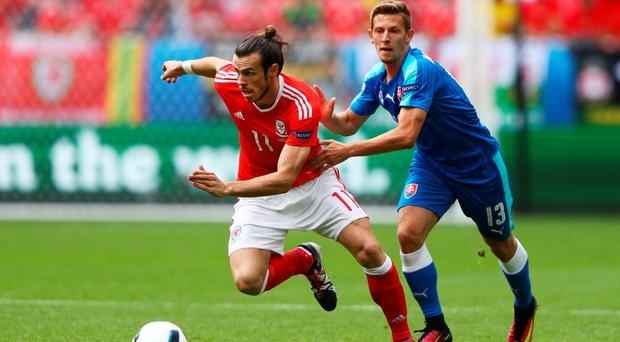 Gareth Bale of Wales and Patrik Hrosovsky of Slovakia compete for the ball during the UEFA EURO 2016 Group B match between Wales and Slovakia at Stade Matmut Atlantique on June 11, 2016 in Bordeaux, France. (Photo by Ian Walton/Getty Images)