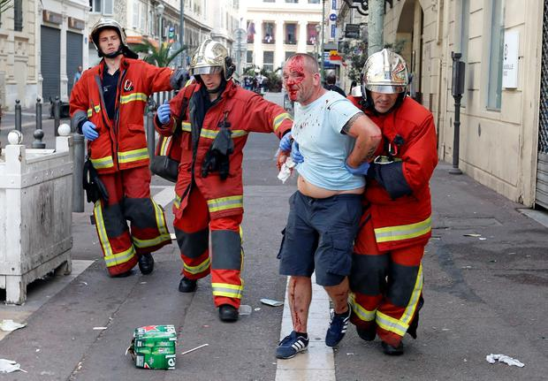 A man is taken away by emergency service workers after he was injured in clashes in downtown Marseille, France, Saturday, June 11, 2016. Riot police have thrown tear gas canisters at soccer fans Saturday in Marseille's Old Port in a third straight day of violence in the city. (AP Photo/Darko Bandic)