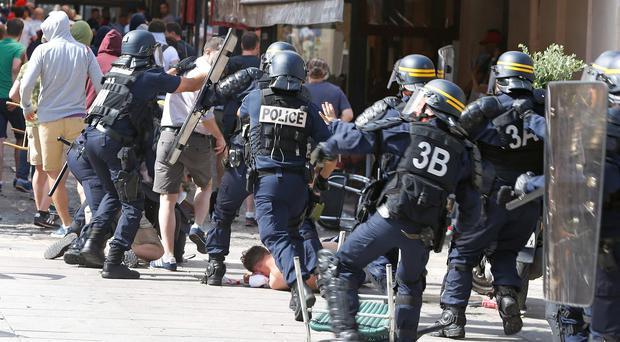 French police officers charge soccer supporters during clashes in downtown Marseille in France